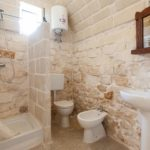 The bathroom, packed with typical Salento stonework