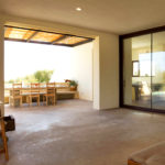 Full length windows lead onto an exterior sitting space with covered dining area