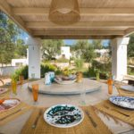 A close view of the tasteful outside dining area beneath a large pergola