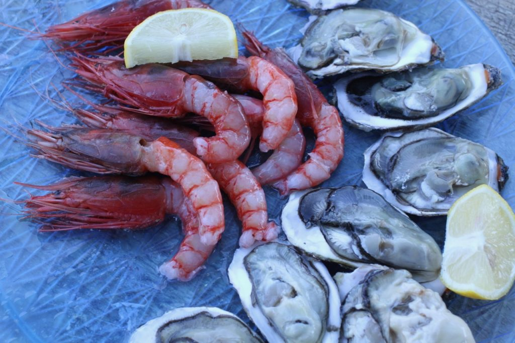 Image of Freshly-caught local delicacies in Gallipoli, giant red prawns and oysters, one of our favourite things to do in Puglia